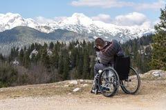 Gehandicapte mens op rolstoel die camera in aard met behulp van, die mooie bergen fotograferen stock afbeeldingen