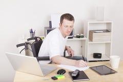Gehandicapte mens in rolstoel thuis bureau royalty-vrije stock afbeeldingen