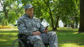 Gehandicapte militaire mens het scrollen smartphonefoto's, rust in stadspark, nostalgie stock footage