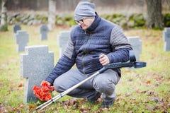 Gehandicapte veteraan met steunpilaren dichtbij aan het grafmonument met bloemen Royalty-vrije Stock Fotografie