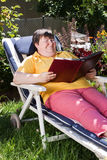 Gehandicapte vrouw die een boek in de tuin leest Stock Foto