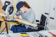 Gehandicapte vrouwelijke werknemer in rolstoel in timmerliedenworkshop stock afbeelding