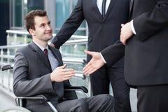 Gehandicapte zakenman het schudden hand met partners Royalty-vrije Stock Foto