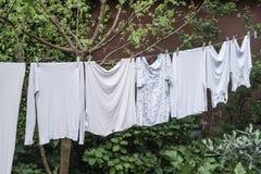 Gehangen kleren bij tuin stock afbeelding