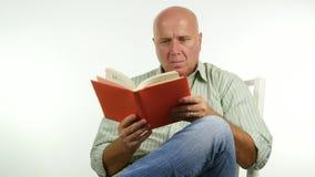 Geheel in beslag genomen businessperson zit op een ontspannen stoel het lezen van een roman stock video