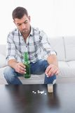 Geheel in beslag genomen mens met een bier en zijn gelegde geneeskunde Royalty-vrije Stock Afbeeldingen