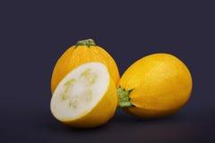 Geheel en besnoeiingscourgettehoogtepunt van voedzame vitaminen op een purpere achtergrond Gezonde groenten van een tuin Royalty-vrije Stock Foto's