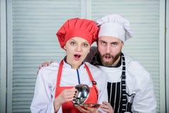 Geheim ingrediënt door recept Eenvormige kok paar in liefde met perfect voedsel Menu planning culinaire keuken Familie stock afbeeldingen