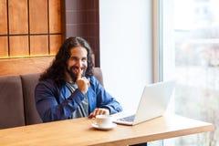 Geheim! Portret van de gelukkige knappe intelligentie jonge volwassen mens freelancer in toevallige stijlzitting in koffie met la stock afbeelding