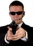 Geheimagent, der eine Gewehr zeigt Stockbild
