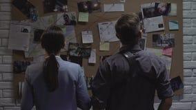 Geheime agentschapteammates die naar misdadige bewegingen op onderzoeksraad zoeken stock footage