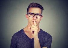 Geheimer Kerl Bemannen Sie das Sagen, dass Stille mit dem Finger auf der Lippengeste ruhig ist, die Kamera betrachtet Lizenzfreies Stockbild