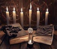 Geheimes Stillleben mit zwei Büchern der schwarzen Magie und brennenden Kerzen Stockfotos