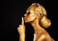 Geheimhaltung. Bodyart. Goldene Frau, die Ruhe-Zeichen zeigt. Stille! Lizenzfreies Stockbild