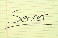 Geheimnis auf einem gelben Kanzleibogenblock Lizenzfreie Stockfotos