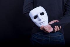 Geheimnismann, der weiße Maske in der Rückseite hält stockfoto