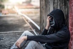 Geheimnismann mit schwarzem Maskengefühl betonte das Sitzen im abandone Stockbilder