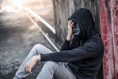 Geheimnismann mit schwarzem Maskengefühl betonte das Sitzen im abandone Lizenzfreie Stockfotografie