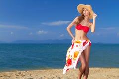 Geheimnistuerische blonde Schönheit in einem roten Bikini Stockbilder