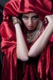 Geheimnisvolle Blondine im roten Satin Lizenzfreie Stockfotos
