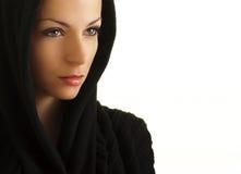 Geheimnisvolle Frau mit einer schwarzen Haube Lizenzfreies Stockfoto