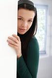 Geheimnisvolle junge Frau, die hinter Wand sich versteckt Lizenzfreie Stockbilder
