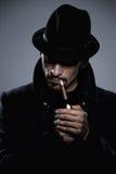 Geheimnisvoller Mann, der eine Zigarette beleuchtet Stockbilder