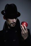 Geheimnisvoller Mann, der einen Apfel anhält Lizenzfreie Stockfotos