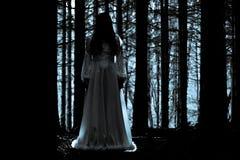 Geheimnisvolles Mädchen im dunklen gespenstischen Wald Lizenzfreie Stockfotos