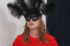 Geheimzinnig mooi blondemeisje in een zwart masker met veren in de studio stock foto's