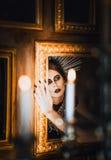 Geheimzinnig portret van mooi gothmeisje die spiegel onderzoeken Royalty-vrije Stock Foto's