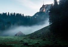 Geheimzinnige berghut en tent tijdens ochtendzonsopgang met mist stock fotografie