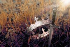 geheimzinnige en magische foto van zilveren koningskroon en zwaard in het hout van Engeland of gebiedslandschap met lichte gloed  royalty-vrije stock foto