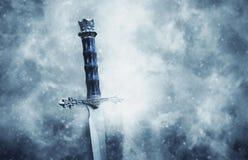 geheimzinnige en magische foto van zilveren zwaard over gotische sneeuw zwarte achtergrond middeleeuws periodeconcept royalty-vrije stock afbeelding