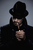 Geheimzinnige mens die een sigaret aansteekt Stock Afbeeldingen