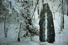 Geheimzinnige oude mens met magisch ijszwaard stock foto