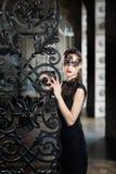 Geheimzinnige vrouw in Venetiaans Carnaval-masker dichtbij smeedijzerpoort Stock Afbeeldingen