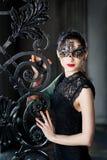 Geheimzinnige vrouw in Venetiaans Carnaval-masker dichtbij smeedijzerpoort Royalty-vrije Stock Fotografie
