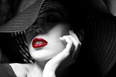 Geheimzinnige vrouw in zwarte hoed. Rode lippen Stock Afbeeldingen