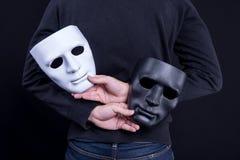 Geheimzinnigheid mens die zwart-wit masker houden stock afbeeldingen