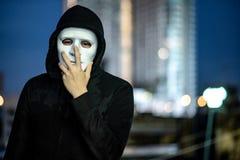 Geheimzinnigheid mens in wit masker die zich op dak bevinden royalty-vrije stock fotografie