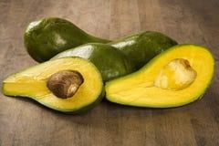 Gehele die avocado's en een avocado in de helft wordt gesneden Stock Foto