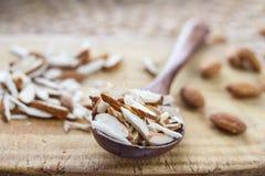 Gehele en gehakte amandelnoten op een houten raad en in een houten eiken lepel op de lijst Stock Foto's