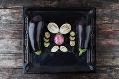Gehele en gesneden aubergines op bakseldienblad Stock Afbeelding