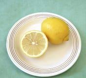 Gehele en halve citroen op plaat Stock Afbeeldingen