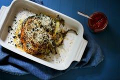 Gehele gebakken couliflower parmezaanse kaasgratin met de saus van de sirarchaspaanse peper stock fotografie