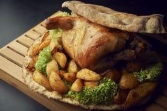 Gehele gebakken kip met aardappelsclose-up op een lijst royalty-vrije stock afbeelding