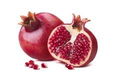Gehele granaatappel halve die zaden op wit worden geïsoleerd