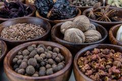 Gehele Notemuskaat en Andere Kruiden in Kommen stock foto