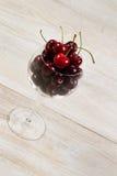 Gehele Rijpe Kersen in Glas op Oud Hout Stock Afbeeldingen